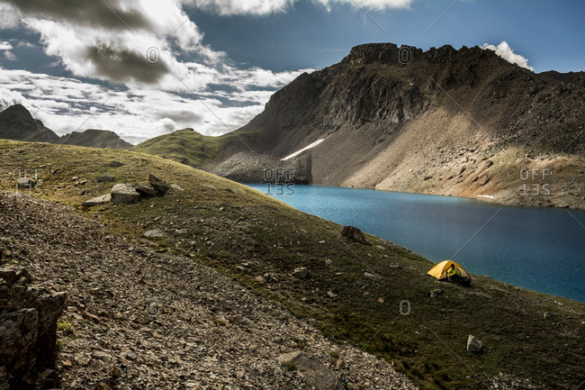 A woman camping near a blue lake, San Juan National Forest, Silverton, Colorado.