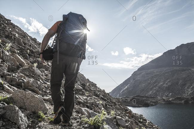 A man hiking along a rocky slope, Rocky Mountain National Park, Estes Park, Colorado.
