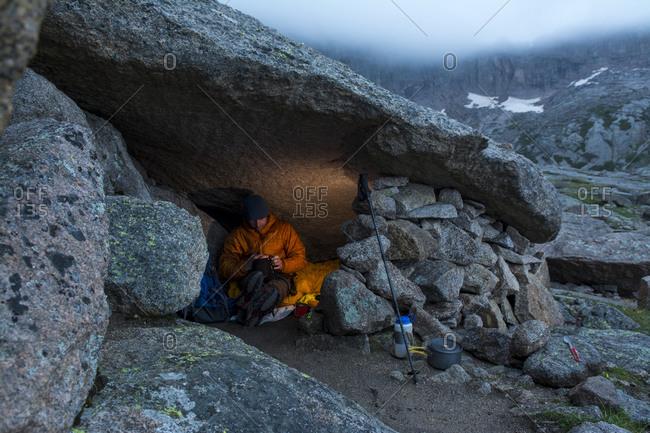 A male mountain climber sitting in a rocky cave, Rocky Mountain National Park, Estes Park, Colorado.