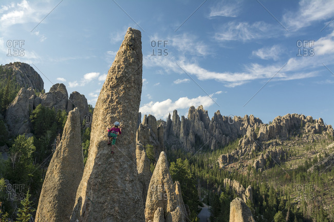 A young girl rock climbing in the Black Hills, Custer State Park, Hill City, South Dakota.