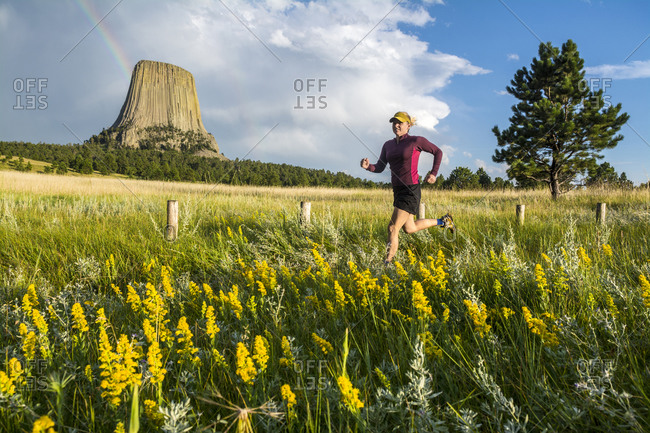 A woman trail running below Devil's Tower, Devil's Tower National Monument, Wyoming.