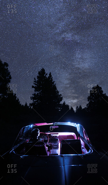Interior of car illuminated under the night sky.