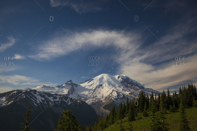 Stars and clouds fill the night sky over Mount Ranier.
