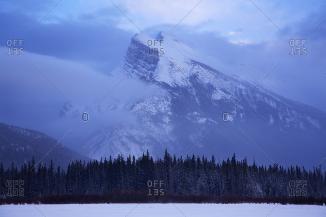 A mountain top behind a snow covered lake in Banff National Park, Alberta, Canada.