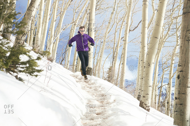 An adult male trail running through a snow covered trail in the mountains of Telluride Colorado.