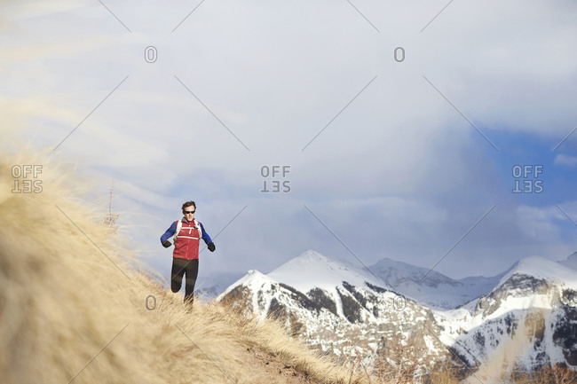 An adult male trail running in the mountains.