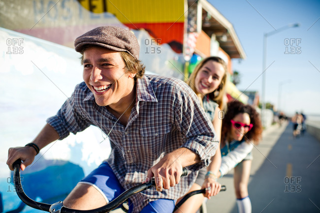Young man smiling as he pedals tandem with two young women behind him on the boardwalk at the beach