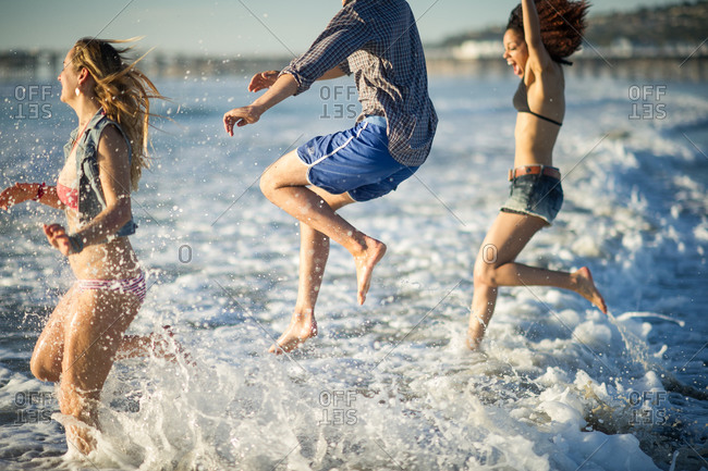 Three young adults having fun as they run in to surf at beach.