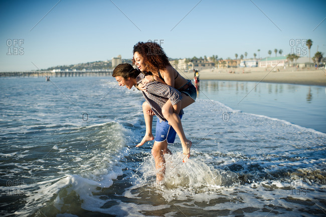 Young man laughs while he carries young woman piggyback into surf.