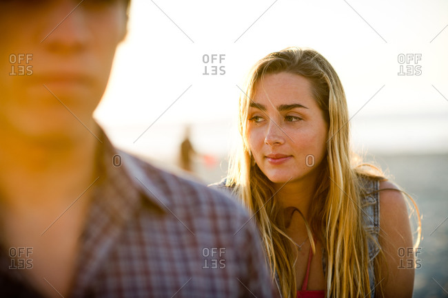 Portrait of young blonde woman at the beach at sunset