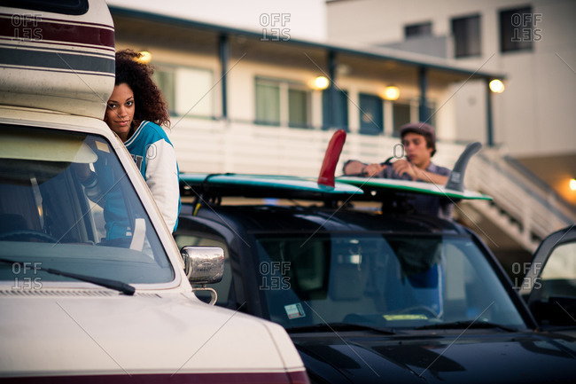 Young woman sits in the window of a vintage camper van as a friend straps surfboard on another car in the background
