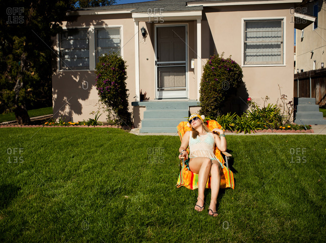 Young woman sitting on beach chair and enjoying sun in front of suburban house.