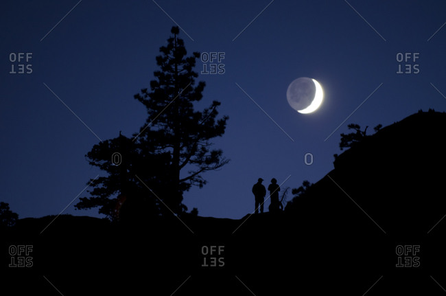 Two people watch the moon rise over the Sierra Mountains in Truckee, California.