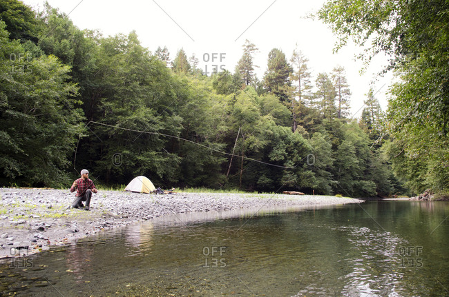 Young man fishes in a river in Redwoods National Park, California.