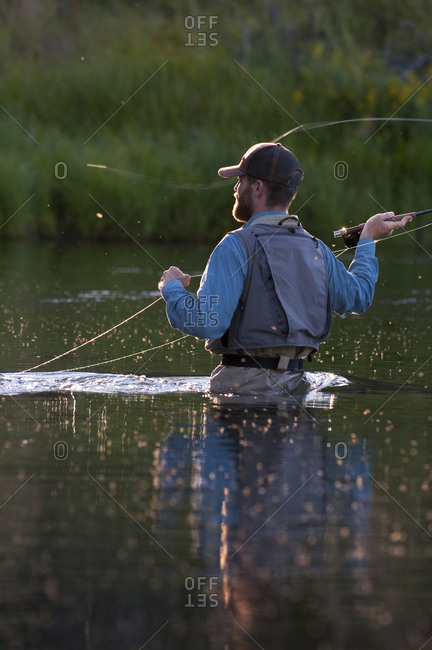 Surrounded by flies, a young man fly fishes in Reno, Nevada.