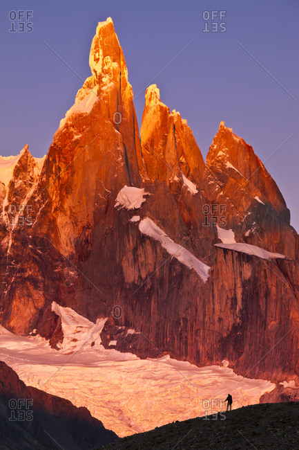 A person is dwarfed in front of Cerro Torre.