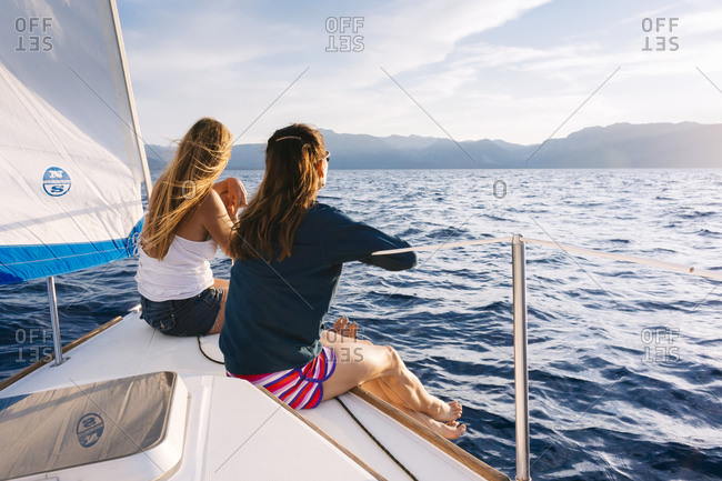 Two women are sitting on a sailboat on Lake Tahoe.