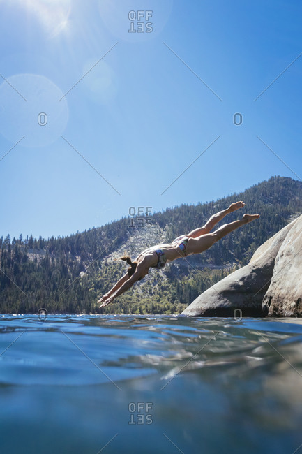 A woman is diving into the water, Lake Tahoe.