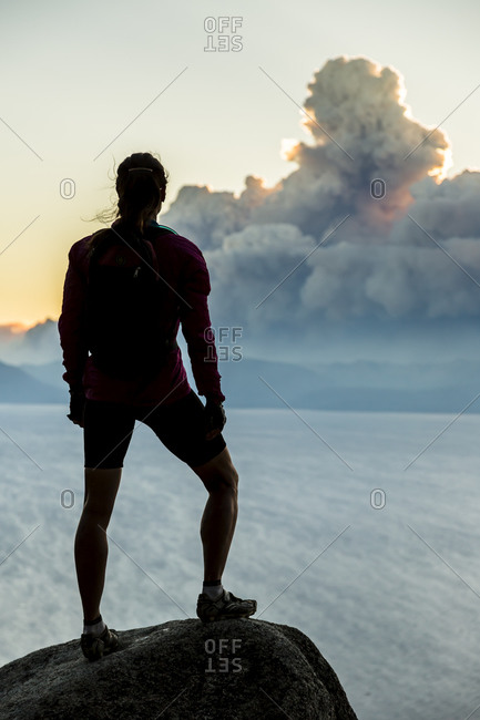 A mountain biker stops on the Flume Trail to watch smoke from a wildfire.