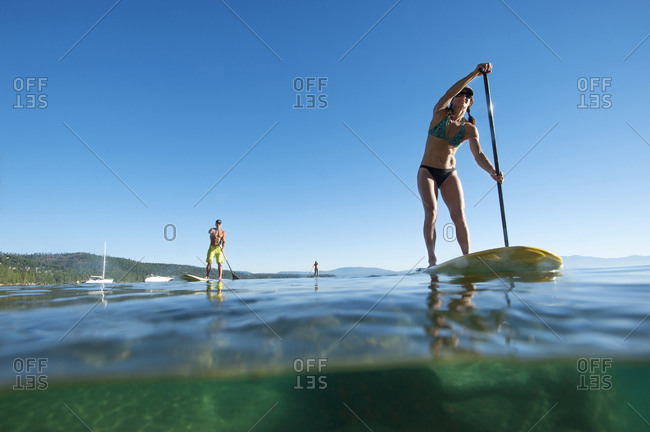 Three people stand-up paddle boarding in Lake Tahoe, California.