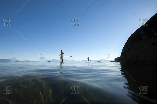 A man and a woman stand-up paddle boarding in Lake Tahoe, California.