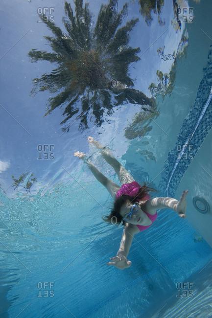 Girl diving toward camera underwater in pool