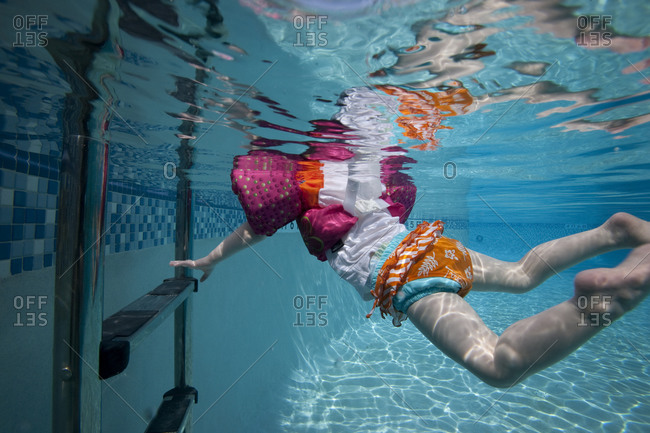 Toddler reaches for pool ladder underwater