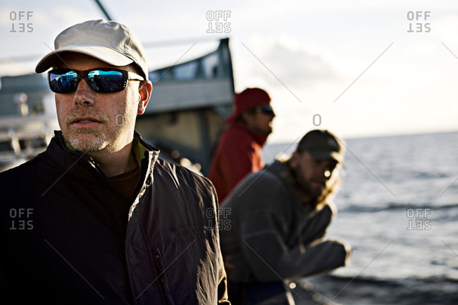 Scientist looks out while standing aboard research boat