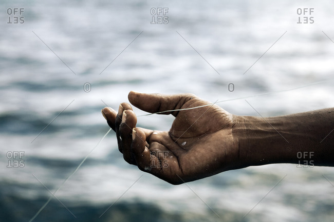 Close-up view of hand holding fishing line with water in the background