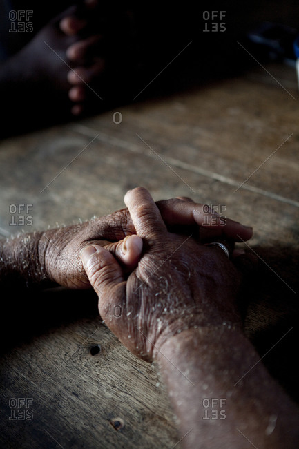 Close-up of old hands crossed and resting on wooden table