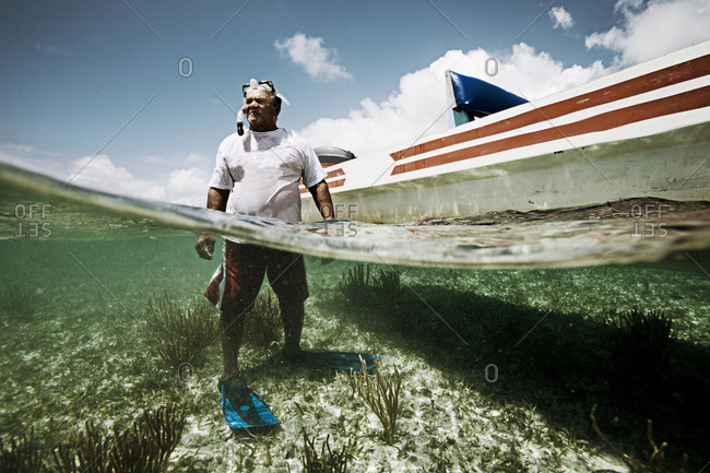 Split level underwater shot of an old man diving for shells from a boat