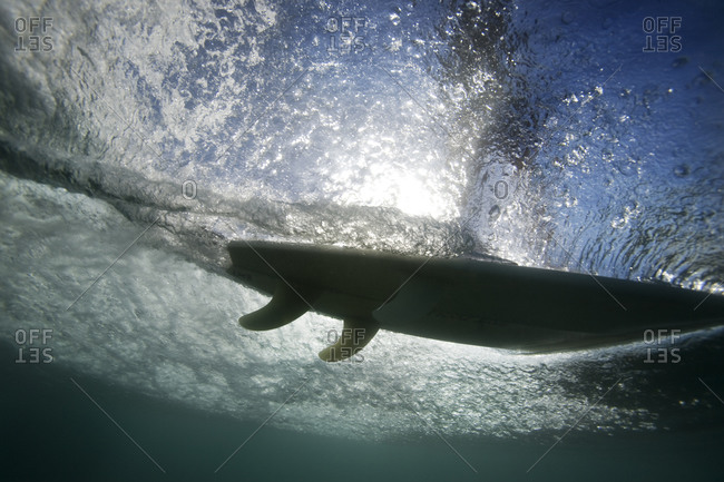 Underwater view of surfboard gliding over water