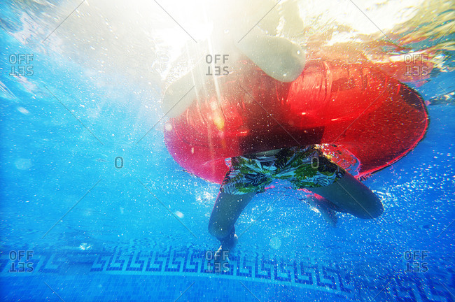 Underwater view of child's legs floating in an inner-tube.