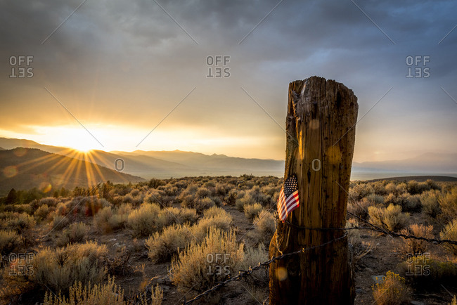 Sunset behind US Flag on lower Summer Meadows Road