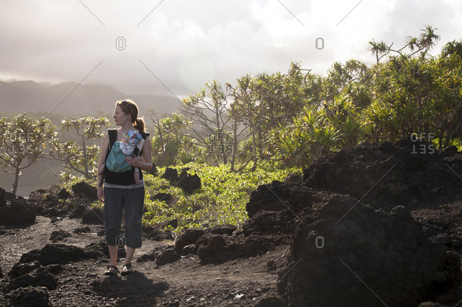 A woman carrying an infant hikes through black sand in Wai'anapanapa State Park.