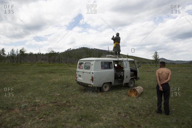 A Mongolian herdsman stands on top of a vehicle in an attempt to get reception for his mobile phone in northern Mongolia.