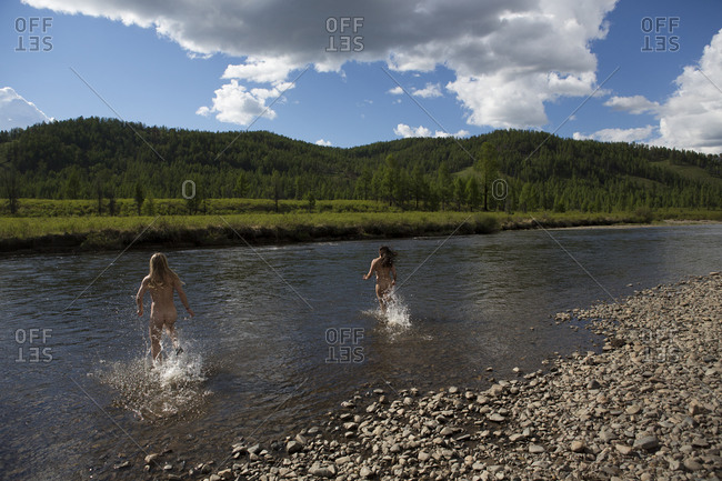Two women run into the Onon River naked to cool off in northern Mongolia.