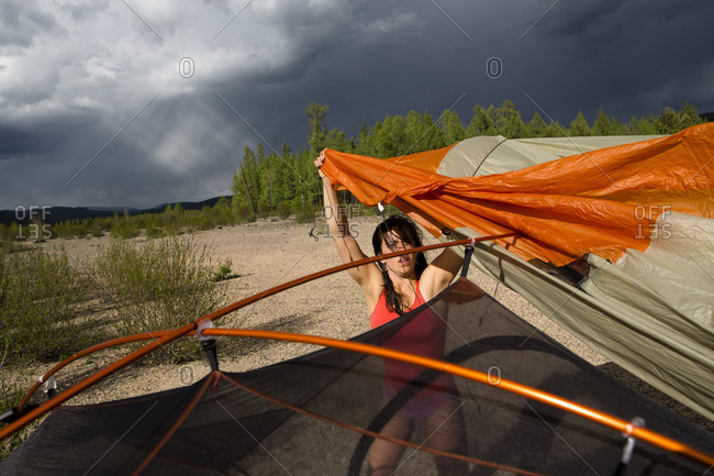 A woman sets up the tent as a monsoonal storm approaches camp on the shore of the Onon River in northern Mongolia.