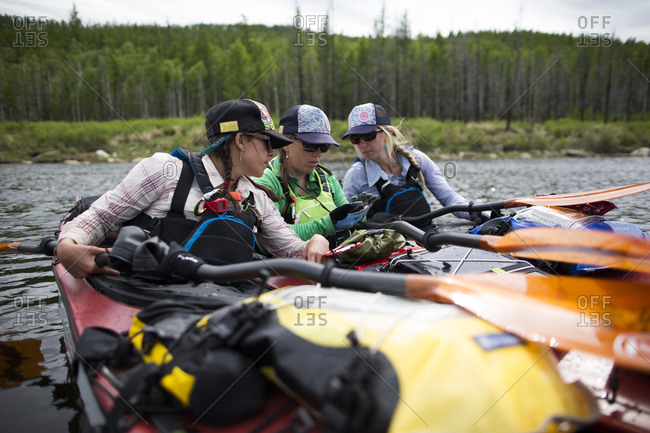 Three women check the GPS for logistical reasons before they continue paddling down the Onon river in northern Mongolia.