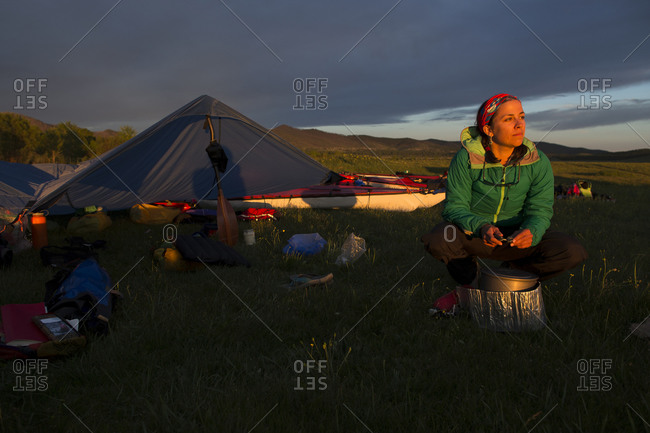 A woman tends to the hot water on the camp stove beside the campsite on the river bank of the Onon river in northern Mongolia.