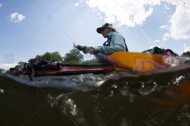 Woman paddles her kayak on Onon river in northern Mongolia.