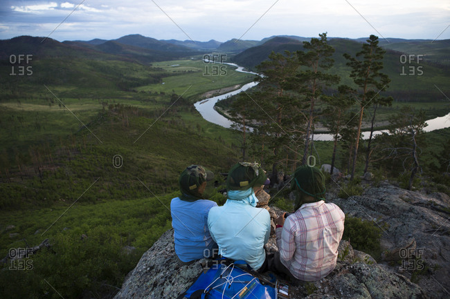 Three women take a moment to reflect over the grand view of the Onon river in northern Mongolia.