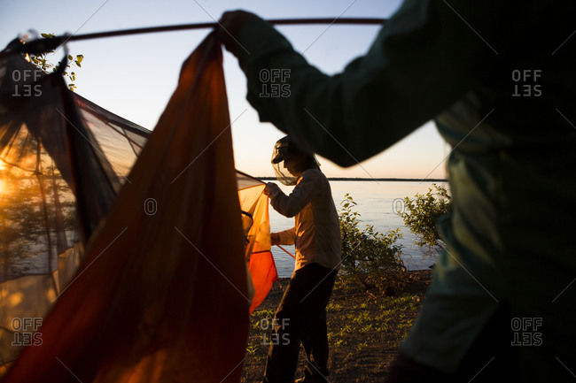 Two woman assemble the tent on the shore of the Amur river in far East Russia.