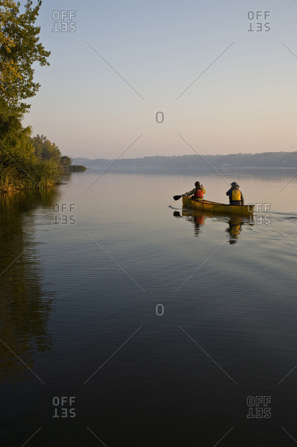 Young couple paddling a canoe in Irondequoit Bay, upstate New York