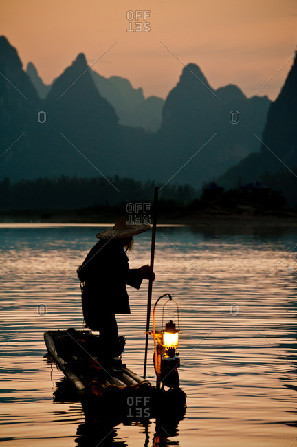 Fisherman on a bamboo boat with mountains in the distance