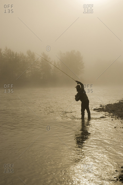 Man angling in the Elk River at East Kootenays, British Columbia, Canada