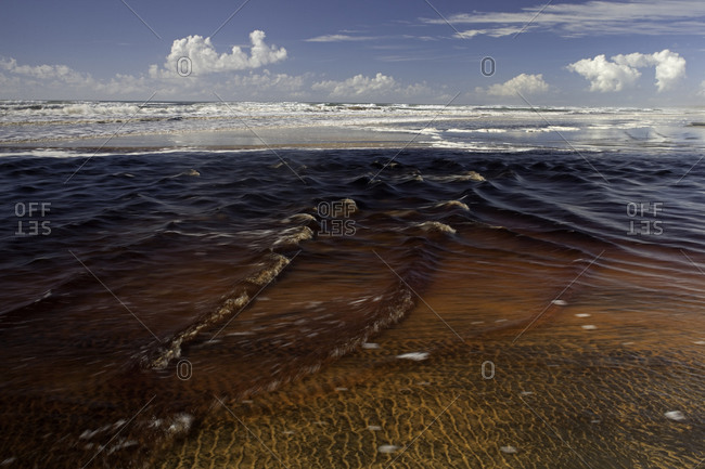 Tannin water from Tooloora Creek entering the ocean,  Fraser Island, Australia