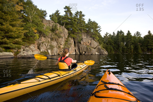 Young woman sea-kayaking on Muskoka River in Ontario, Canada