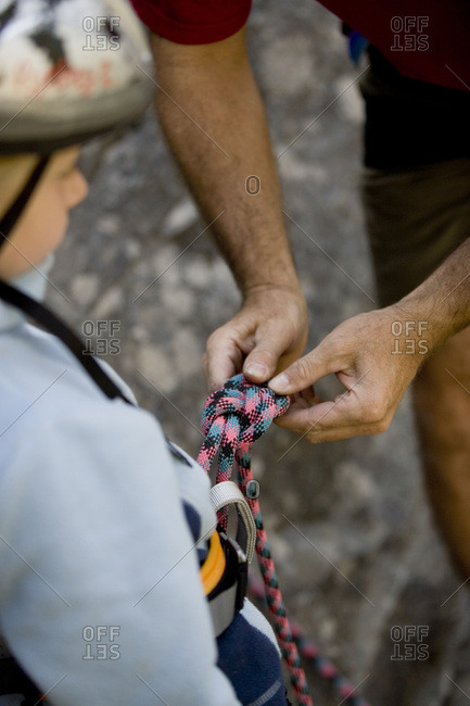 Man helping his daughter to tie the climbing rope in Montana, USA