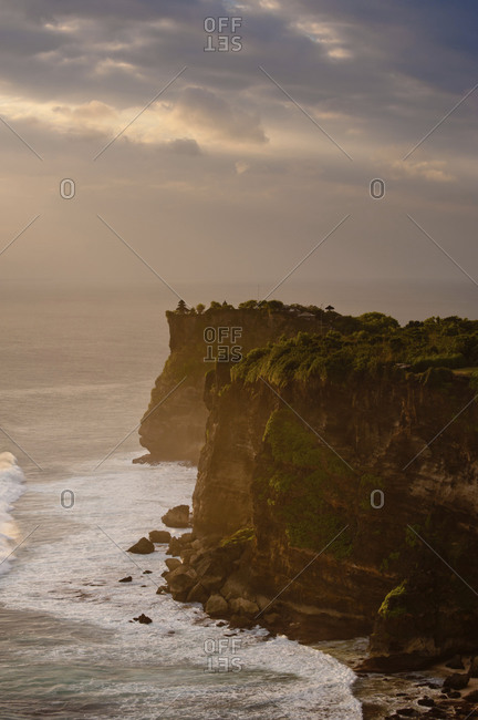 Ocean breaking against cliffs at sunset in Bali, Indonesia